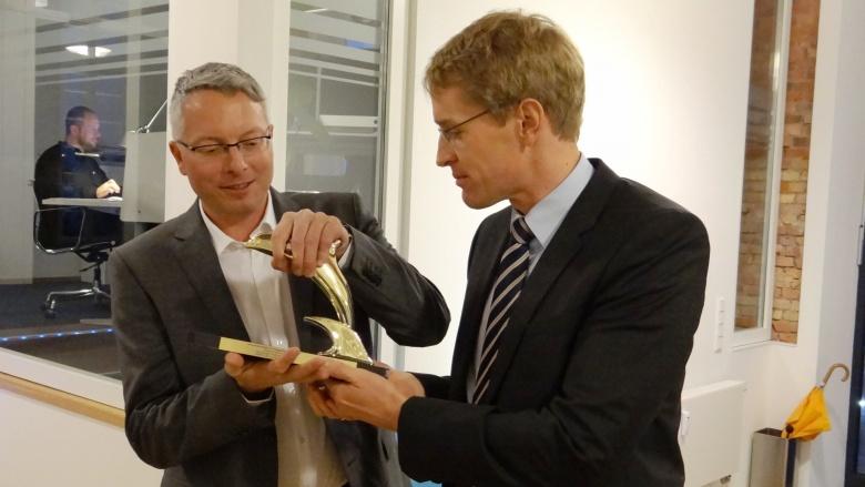 Daniel Günther, MdL, mit Arne Rüstemeier und dem goldenen Delphin aus Cannes bei bewegtbild in Flensburg